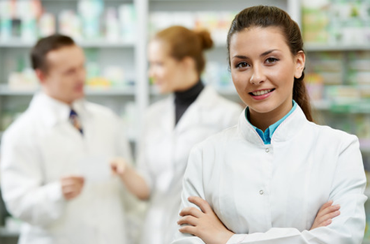 Smiling pharmacist standing in a pharmacy