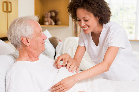 Caring nurse helping elderly patient